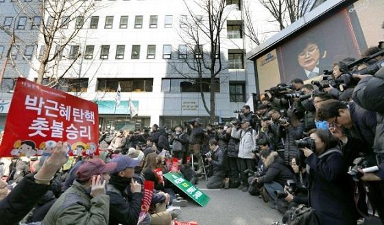 韓国の朴槿恵大統領の罷免を求める集会で、決定言い渡しの行われる憲法裁判所のテレビ中継を見る参加者ら(10日、ソウル)=共同
