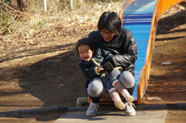 巨大ローラー滑り台を滑る子供と母親